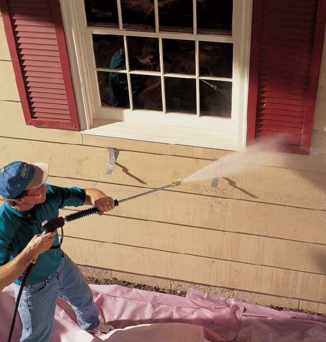Image of empoyee pressure washing a customers' house.