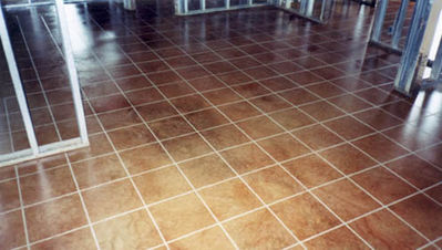 Image of acid stained floor with square tile patten etched in.